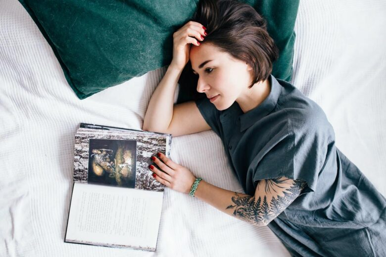 Girl with book laying on the bed